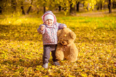 Mädchen, das mit Teddybären am Herbstpark geht Stockfoto