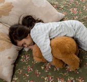 Mädchen, das mit Teddybären schläft Lizenzfreie Stockfotografie