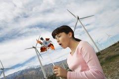 Mädchen, das mit Toy Windmill At Wind Farm spielt Lizenzfreie Stockfotos