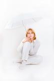Mädchen, das mit weißem Regenschirm overwhite sitzt Stockfotos