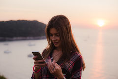 Mädchen, das Mobiltelefon nahe dem Meer im Sonnenaufgang oder im Sonnenuntergang verwendet Stockbilder