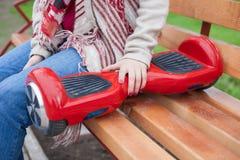 Mädchen, das modernen roten elektrischen mini segway oder Schwebeflugbrettroller hält Lizenzfreies Stockfoto