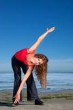 Mädchen, das Morgenübungen am Strand tut Stockbild