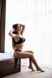 Mädchen, das am Morgen des Betts morgens nahe Fenster sitzt Stockfoto
