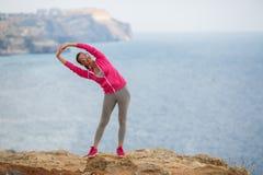 Mädchen, das morgens Gymnastik auf dem Strand-Ozean tut Lizenzfreies Stockfoto