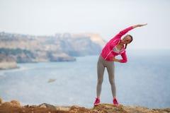 Mädchen, das morgens Gymnastik auf dem Strand-Ozean tut Lizenzfreies Stockbild