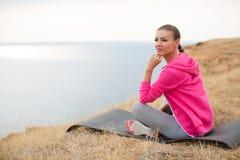 Mädchen, das morgens Gymnastik auf dem Strand-Ozean tut Stockfoto