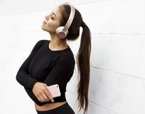 Mädchen, das Musik auf weißem Hintergrund hört lizenzfreie stockbilder