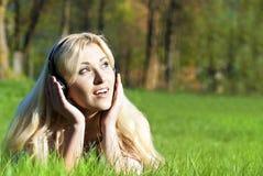 Mädchen, das Musik in der Natur hört Stockbild