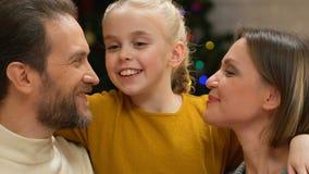 Mädchen, das Mutter und Vati auf Backen, Liebe und Sorgfalt zeigend der Familie auf Weihnachten küsst stock video