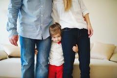 Mädchen, das Mutter und Vati für Beine umarmt Stockbilder