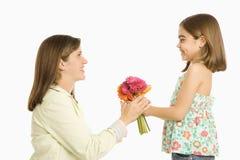 Mädchen, das Mutterblumen gibt. Stockfoto