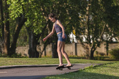 Mädchen, das nach Hause Skateboard fährt Stockbild