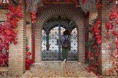 Mädchen, das nach innen vom dekorativen gewölbten Eisenzugang durch Ziegelsteintür schaut lizenzfreie stockfotografie