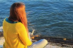 Mädchen, das nahe bei dem Riverbank bei Sonnenuntergang in Lissabon sitzt stockbild