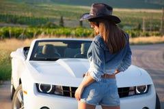 Mädchen, das nahe bei einem weißen Cabriolet steht Stockbilder