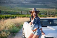 Mädchen, das nahe bei einem weißen Cabriolet steht Lizenzfreie Stockfotografie