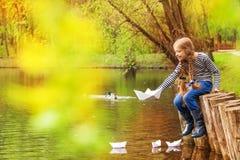 Mädchen, das nahe dem Teich spielt mit Papierbooten sitzt Stockbild