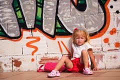 Mädchen, das nahe der Wand sitzt stockfotos