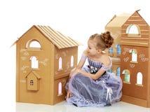 Mädchen, das nahe einem Haus gemacht von der Pappe aufwirft Lizenzfreie Stockfotos