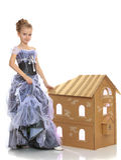 Mädchen, das nahe einem Haus gemacht von der Pappe aufwirft Stockbild
