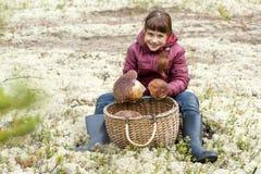 Mädchen, das nahe einem Korb mit Pilzen sitzt Lizenzfreie Stockfotos