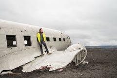 Mädchen, das nahe remainings des zerschmetterten Flugzeuges aufwirft Lizenzfreie Stockbilder