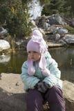 Mädchen, das nahe Teich sitzt lizenzfreie stockfotografie