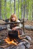 Mädchen, das nahe vom Feuer im Wald sitzt Lizenzfreies Stockbild