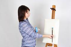 Mädchen, das nahes Gestell und das Malen steht Lizenzfreie Stockfotos