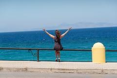 Mädchen, das neben der Straße mit Ansichten des Meeres sitzt Stockbild
