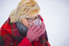 Mädchen, das oben heißen Tee im Winterwald, Abschluss trinkt Stockfotos