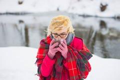 Mädchen, das oben heißen Tee im Winterwald, Abschluss trinkt Stockbild