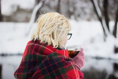 Mädchen, das oben heißen Tee im Winterwald, Abschluss trinkt Lizenzfreie Stockfotos