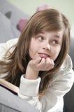 Mädchen, das oben von ihrem Buch schaut Lizenzfreie Stockfotos