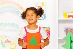 Mädchen, das orange Kartonkarte mit Weihnachtsbaum hält Lizenzfreie Stockbilder