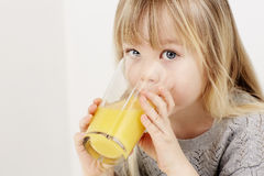 Mädchen, das Orangensaft trinkt Stockbild