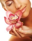 Mädchen, das Orchideenblume in ihren Händen hält Lizenzfreies Stockfoto