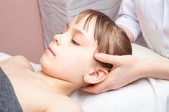 Mädchen, das osteopathic Behandlung ihres Kopfes bekommt Stockbild