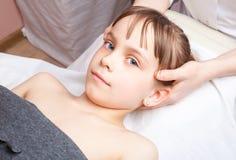 Mädchen, das osteopathic Behandlung ihres Kopfes bekommt Stockfotos