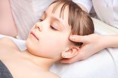 Mädchen, das osteopathic Behandlung ihres Kopfes bekommt Stockbilder