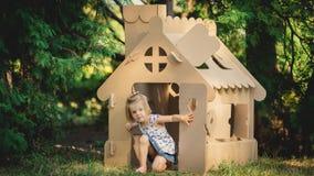 Mädchen, das Papphaus in einem Stadtpark spielt Stockfotos