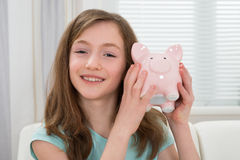 Mädchen, das Piggy Querneigung anhält Stockfotografie
