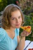 Mädchen, das Pizza isst Stockfotos