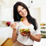 Mädchen, das positiv schaut und ein gebrüllte mit Salat hält Stockbild
