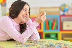 Mädchen, das Puzzlespiele sammelt Stockbild