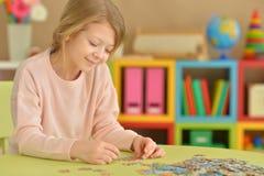 Mädchen, das Puzzlespiele sammelt Stockfotos