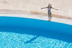 Mädchen, das am Rand des Pools ein Sonnenbad nimmt Lizenzfreies Stockfoto