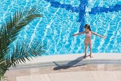 Mädchen, das am Rand des Pools ein Sonnenbad nimmt Stockbilder