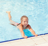 Mädchen, das am Rand des Pools sitzt Lizenzfreie Stockbilder